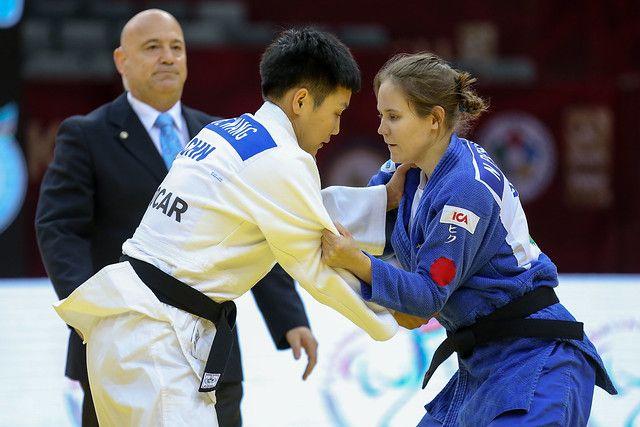 Nicolina Pernheim greppar motståndaren i en match på Grand Prix i Baku 2019. Båda står upp. I bakgrunden syns en domare.