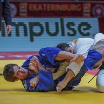 Tommy Macias attackerar med ett armlåsförsök nere i mattan.