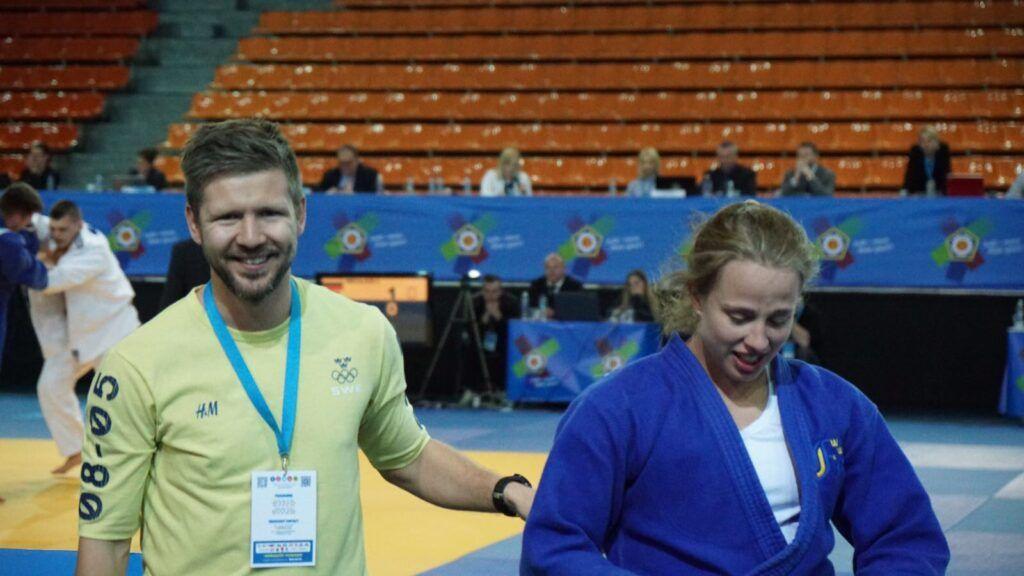 Johan Berg ler och går av tävlingsmattan tillsammans med Ida Eriksson som han coachat under en europacup i judo. I bakgrunden syns två andra som tävlar och banderoller med EJU:s logotyp.