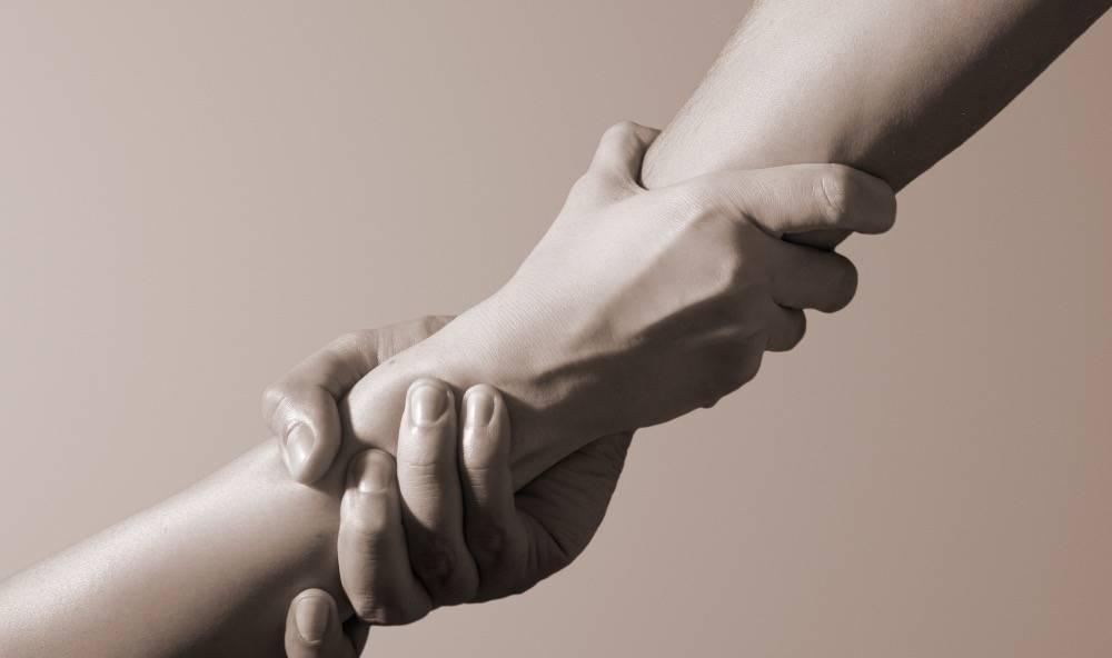 Två händer möts och håller varandra om handleden i en hjälpande gest.