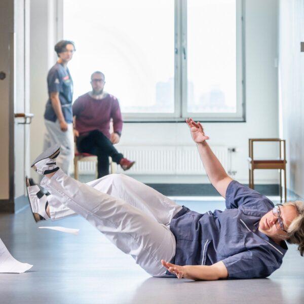 Kvinna som arbetar i sjukvården faller på ett golv.