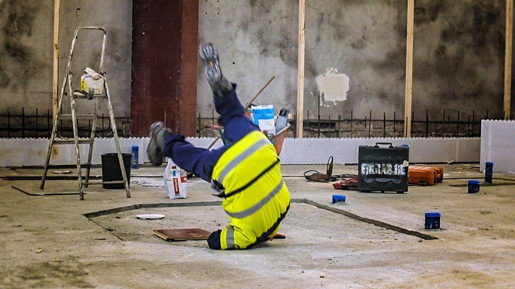 Man i byggkläder i industrilokal faller framåt och rullar över axeln.
