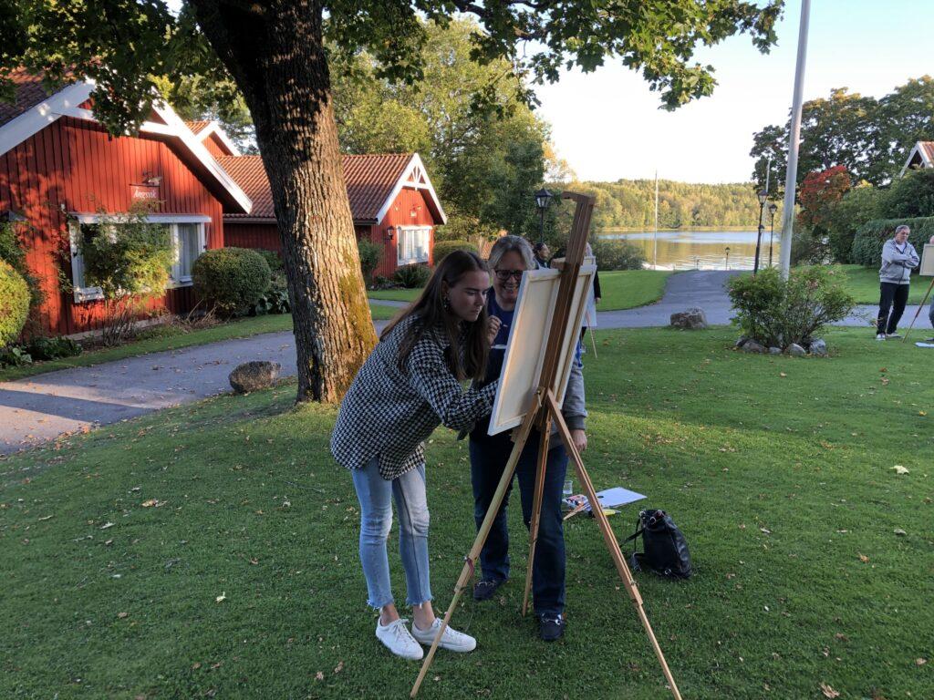 Två stycken står och målar på en tavla på ett stativ.