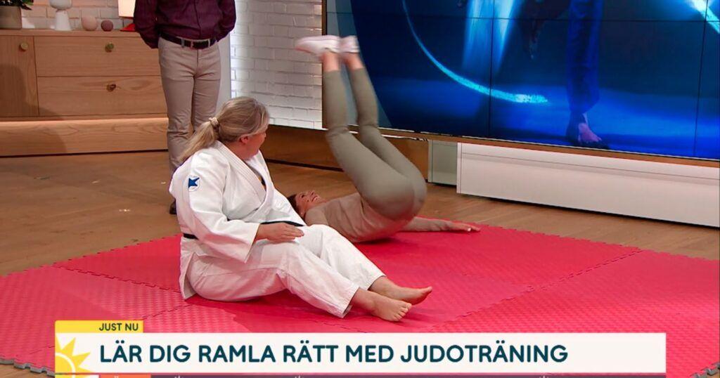 Judoinstruktör sitter på judomatta i studion på TV4. Bredvid rullar programledaren bakåt på rygg för att öva bakåtfall.