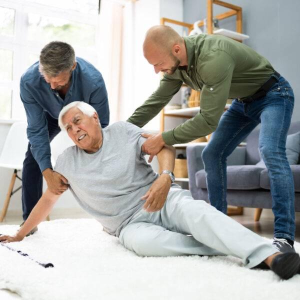 Två män hjälper en äldre man som fallit i hemmiljö.