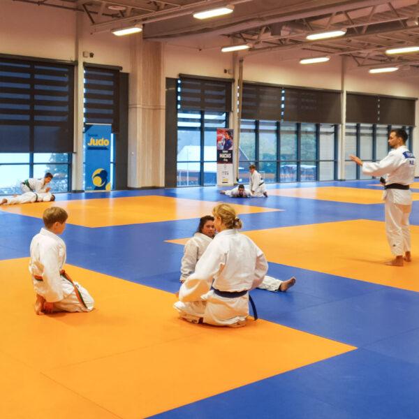 Barn sitter på judomattan och väntar på instruktioner från tränaren.