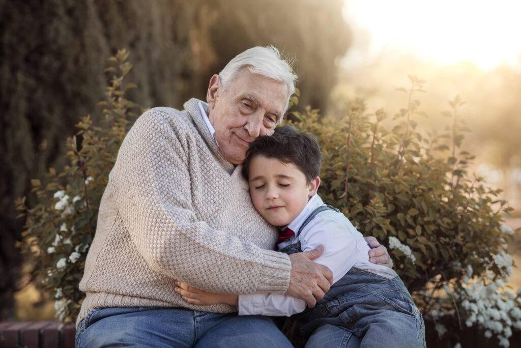En äldre man och en pojke sitter på en bänk och kramas.