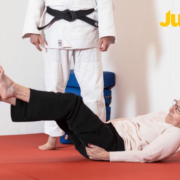 Äldre kvinna ligger på rygg på judomatta och håller upp huvudet och fötterna från golvet. Instruktör i judodräkt står bakom.
