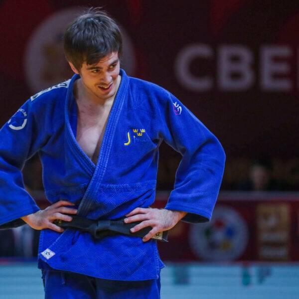 Tommy Macias i blå judodräkt står med armarna i sidan och tittar snett nedåt.