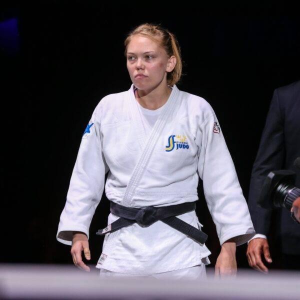 Anna Bernholm i vit judodräkt ser bestämd ut. Landslagschef Robert Eriksson går bakom.