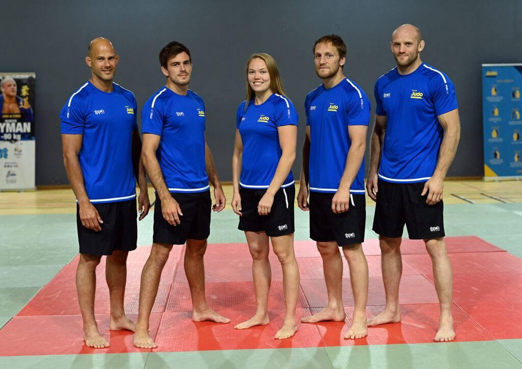 Landslaget står uppställda på rad klädda i svarta shorts och blå t-shirt.