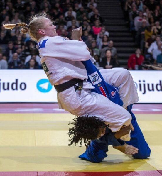 Anna Bernholm har klättrat upp på motståndare och håller dennes arm hårt, nära kroppen och lutar sig bakåt.