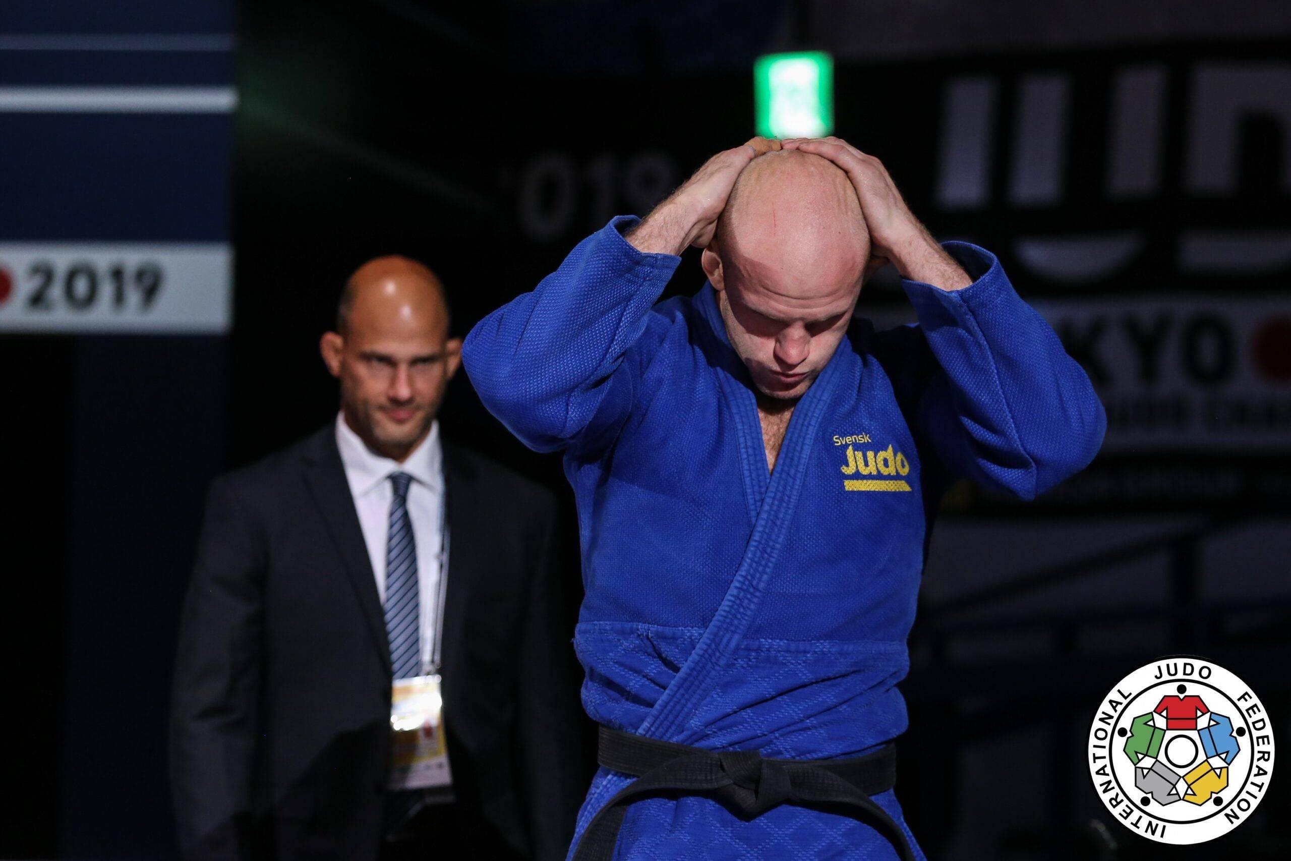 Marcus Nyman i blå judodräkt går in på arenan. Tittar ner och håller båda händer knäppta bakom huvudet. Landslagschef Robert Eriksson går bakom.