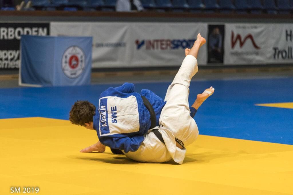 Alexander Dahlin i blå judodräkt försöker trycka ner sin motståndare i mattan.