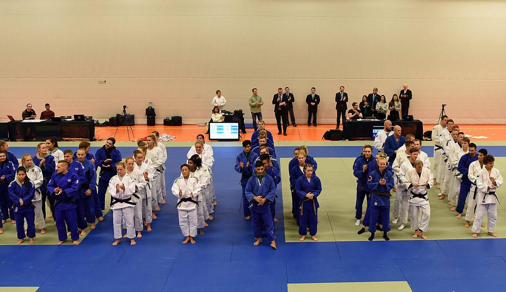 Tävlande står uppställda på judomattan i rader i sina lag.