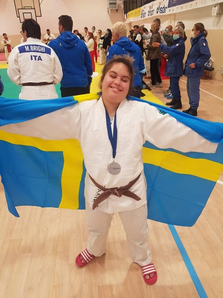 Amanda Orrbo i vit judodräkt med silvermedalj runt halsen. Håller upp en svensk stor flagga bakom ryggen.