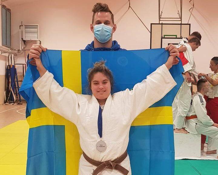 Amanda Orrbo i vit judodräkt med silvermedalj runt halsen. Bakom henne svenska flaggan och tränaren Jonathan Fagerhill.
