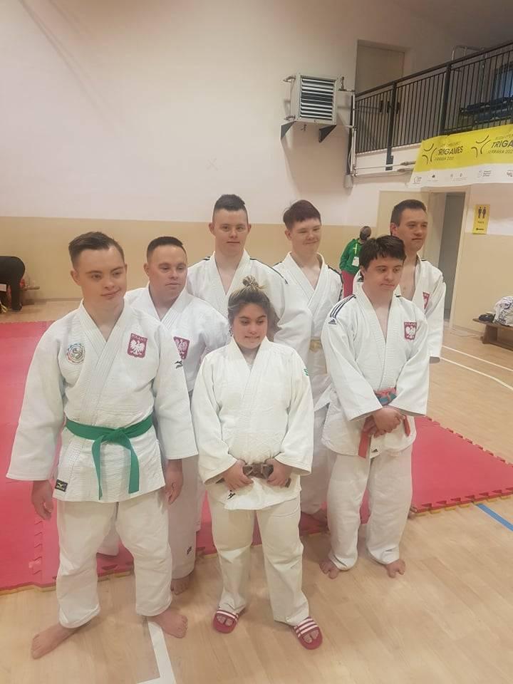 Amanda Orrbo och sex andra judoka i det polska laget står bredvid varandra i vit judodräkt.